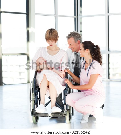 Mother with her newborn baby and doctors in hospital - stock photo