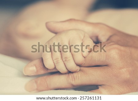 Mother with her newborn baby care hands - stock photo