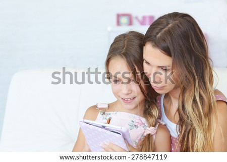 Mother with her preteen daugher playing ipad together - stock photo