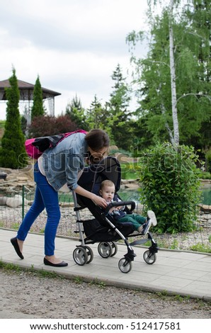 Mother with her small baby bo are walking in the park