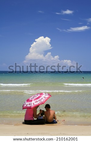 Mother  with her son and daughter playing on the beach - stock photo