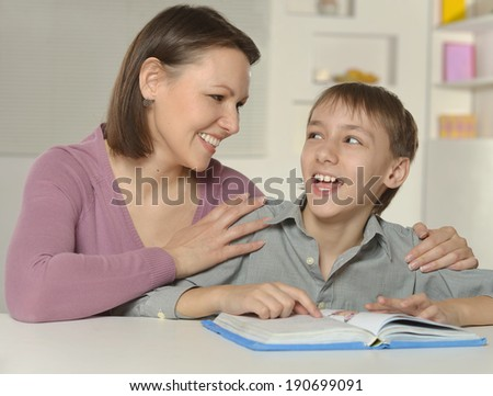 Mother with her son doing homework at home - stock photo