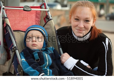 mother with her son in pram against outdoor - stock photo