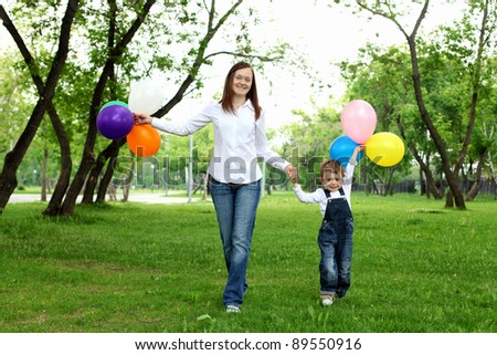 Mother with her son in the summer park with balloons - stock photo
