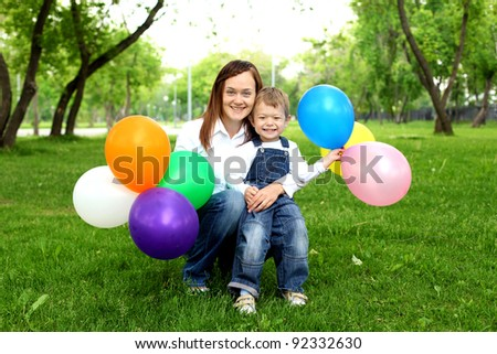 Mother with her son in the summer park with baloons - stock photo