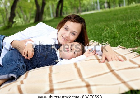 Mother with her son outside in the summer park - stock photo