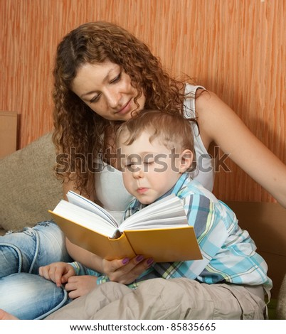mother with her son reading book on sofa - stock photo