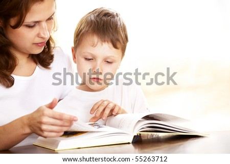 mother with her son reading indoor - stock photo
