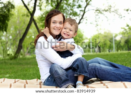 Mother with her son sitting and embracing in the summer park