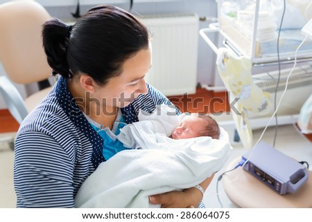 Mother with her tiny son in the hospital - stock photo