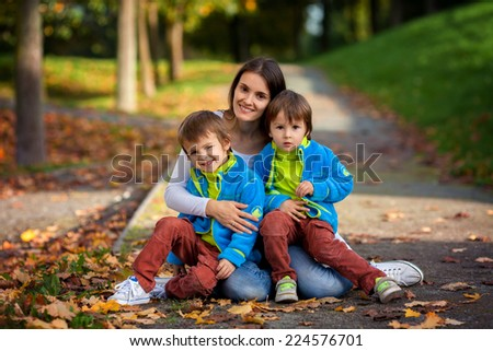 Mother with her two boys in the park in autumn day - stock photo