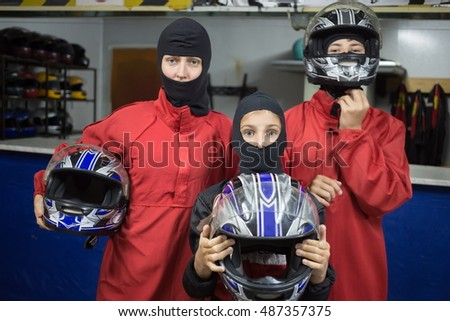 Mother with her two children are standing in helmet at carting, focus on girl.