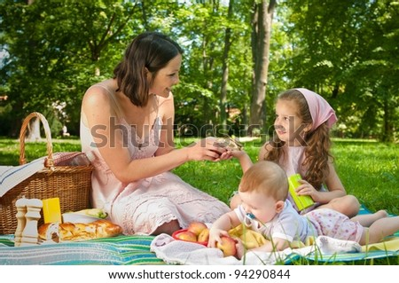 Mother with her two children having picnic in park - baby in front - stock photo