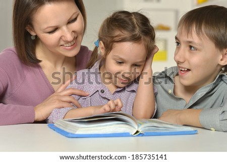 Mother with her two kids doing homework - stock photo