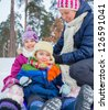 Mother with her two kids is sledging in winter-landscape. Focus on the boy. - stock photo