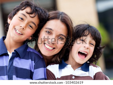 Mother with her two sons looking happy and smiling - stock photo