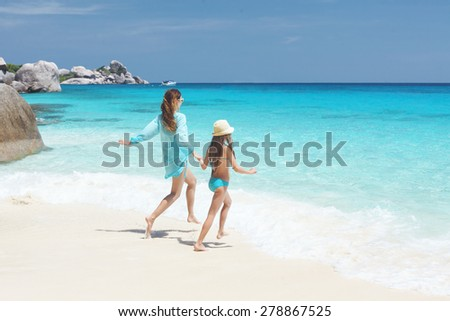 Mother with her 8 years old daughter resting on a tropical beach during summer vacations - stock photo