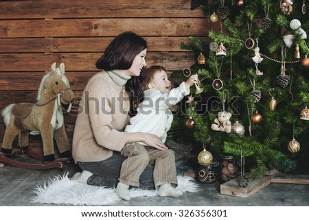 Mother with her 3 years old son celebrating holidays near Christmas tree, farm house design - stock photo