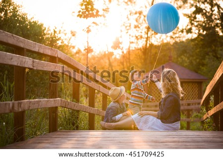 Mother with kid boy and cute little toddler sitting on wooden bridge and playing with blue balloon on summer sunset. Woman with children outdoors. Lifestyle concept - stock photo