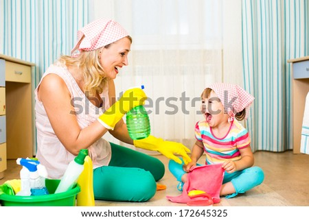 mother with kid cleaning room and having fun - stock photo