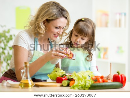 mother with kid make vegetable salad at kitchen - stock photo