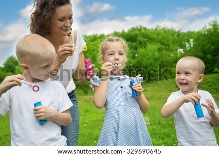 Mother with kids blowing bubbles outdoors.