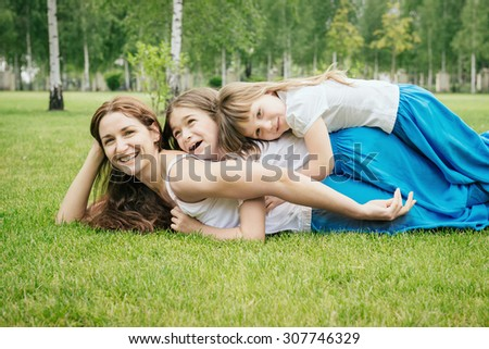 Mother with kids having fun playing outdoors. Family has the same clothes. Happy children lie on mom's back  - stock photo