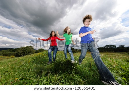Mother with kids jumping outdoor - stock photo