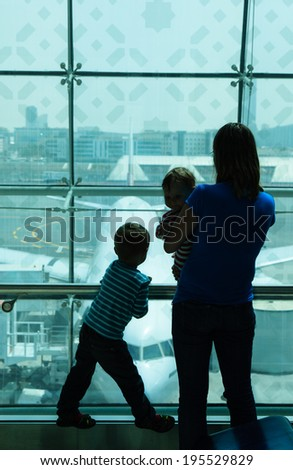 mother with kids looking at planes while waiting in the airport - stock photo