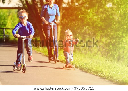 mother with kids riding scooters in summer - stock photo