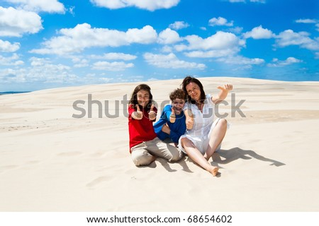 Mother with kids sitting on dunes - stock photo