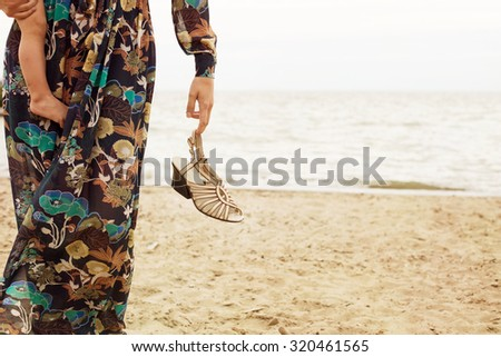Mother with little baby daughter walking on the beach. Family time outdoor - stock photo
