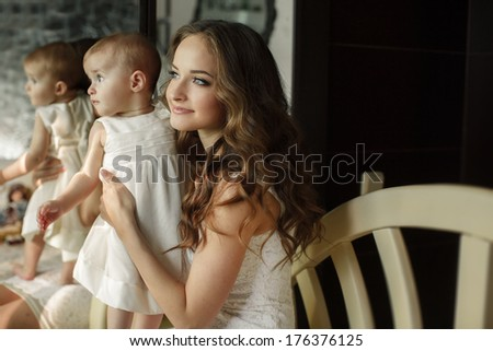 Mother with little baby in home interior young beautiful mom hugging daughter, pretty brunet woman playing with cute small girl, smiling girl holding adorable sweet child, happy family concept - stock photo