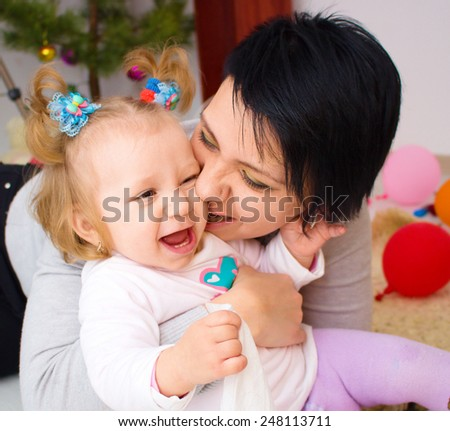 Mother with little baby, young beautiful mom hugging doter, pretty brunet woman playing with cute small girl, smiling girl holding adorable sweet child, happy family concept - stock photo