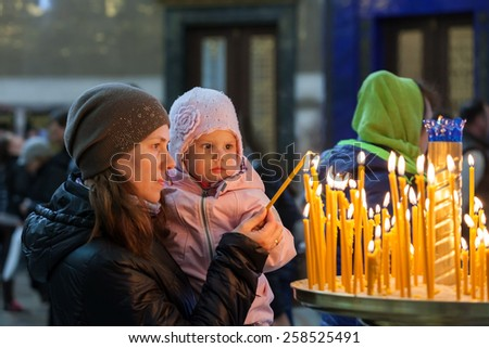 Mother with little blond Caucasian daughter in Orthodox Russian Church - stock photo