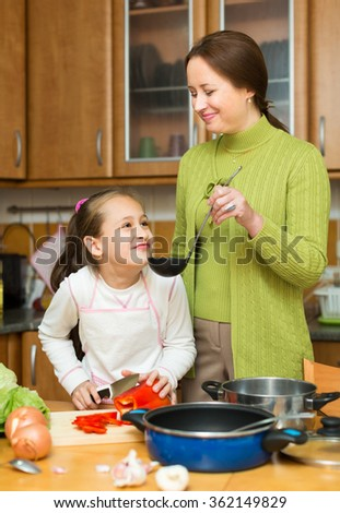 Mother with little cheerful daughter cooking at home kitchen together and smiling. Focus on woman - stock photo