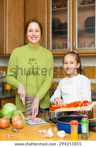 Mother with little cheerful daughter cooking together at home kitchen and smiling. Focus on girl - stock photo
