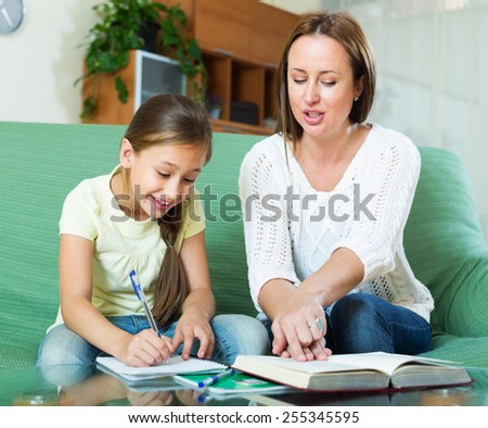 mother with little daughter  doing homework together in home  - stock photo