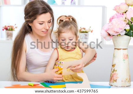 mother with little daughter in a yellow dress fun cut scissors colored paper - stock photo