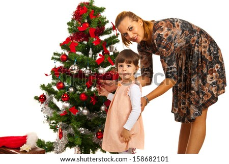 Mother with little daughter in front of Christmas tree - stock photo