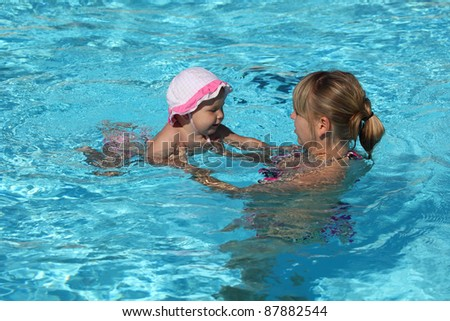 Mother with little daughter in the swimming pool