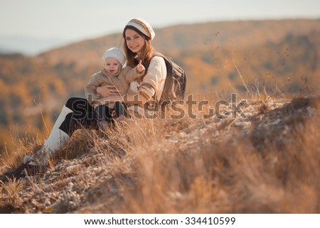 Mother with little daughter resting in autumn mountains