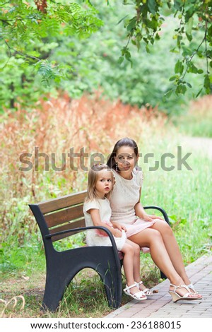 mother with little daughter sits on a bench in the Park - stock photo