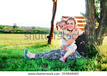 mother with little daughter sitting hugging in the park, communication with children, parenting, nature, fresh air