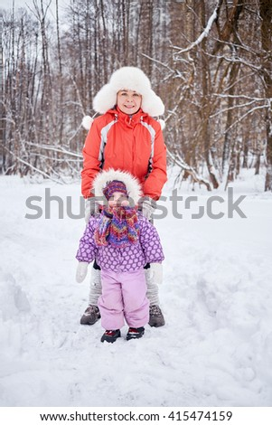 Mother with little daughter stand in snowy winter park. - stock photo