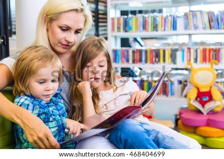 Mother with little girl and boy read book together. Happy family, pre-school concept. Parent educating children.