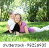 Mother with little son in the park reading a book - stock photo
