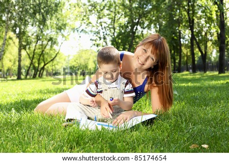 Mother with little son in the park reading a book