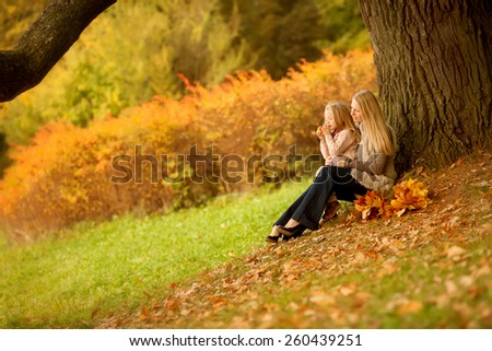 mother with long blond hair and her pretty daughter are sitting and playing under the tree in the the beautiful autumn park  - stock photo