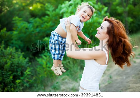 Mother with long curly red hair playing with her son in the park. Happy family enjoying relaxing and enjoying life in nature. Outdoor shot. Copyspace - stock photo